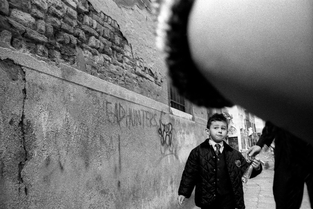 A documentary photograph of a boy walking down the streets of italy