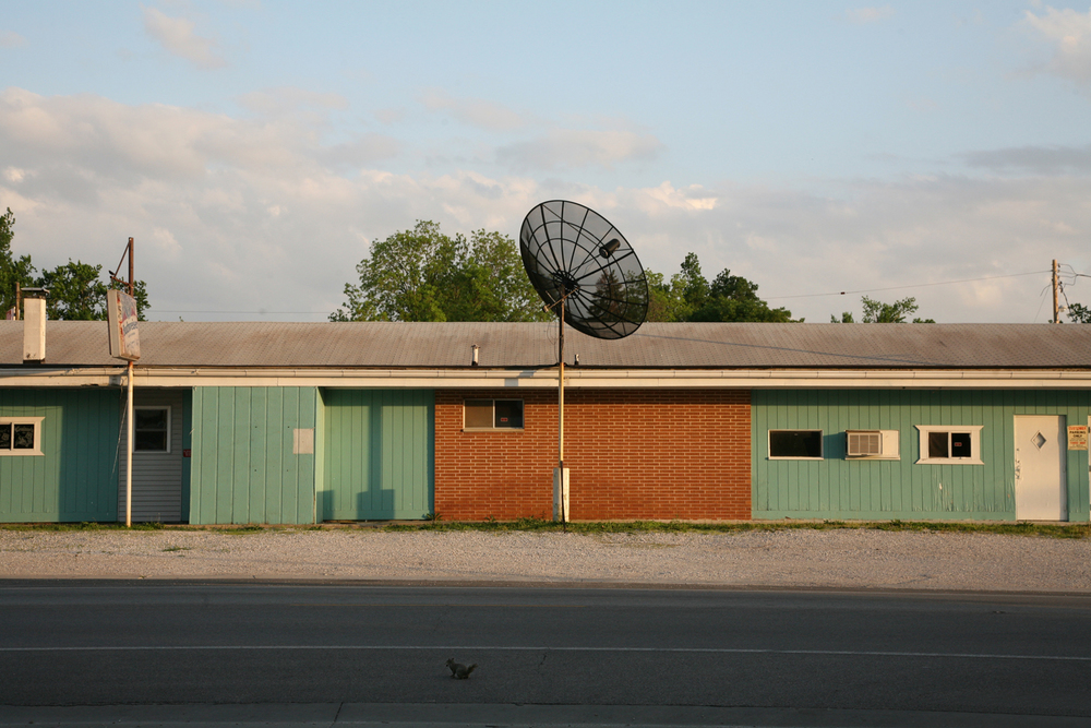 A documentary photograph of a building with a satellite dish in the midwest of the united states.