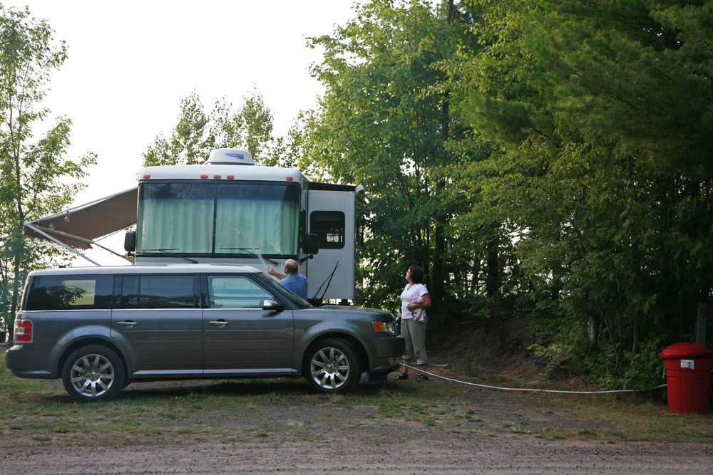 A documentary photograph of a couple washing their recreational vehicle during a camping trip in the midwest of the united states