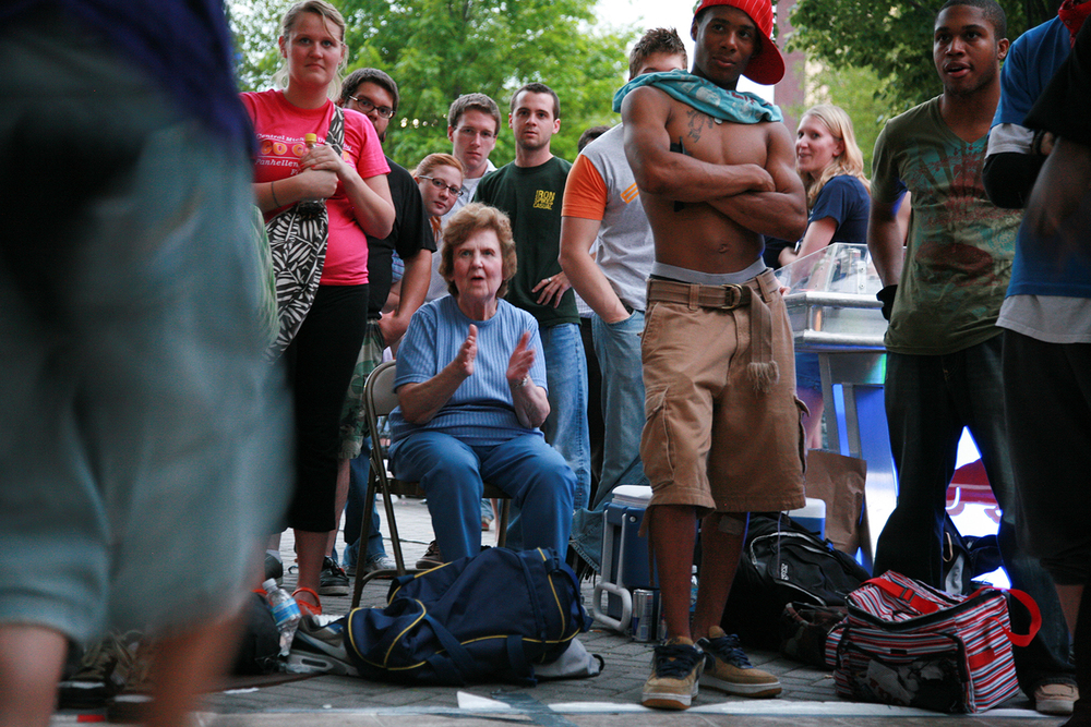 A documentary photograph of an older woman clapping for break dancers during a festival in the midwest of the united states
