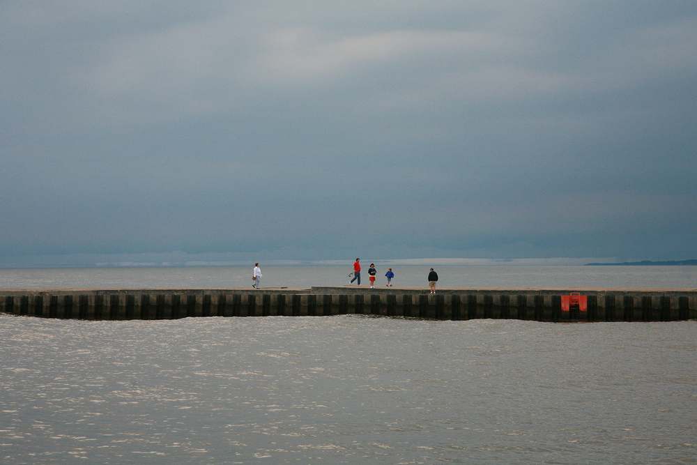 A documentary photograph of people walking along the pier in lake michigan