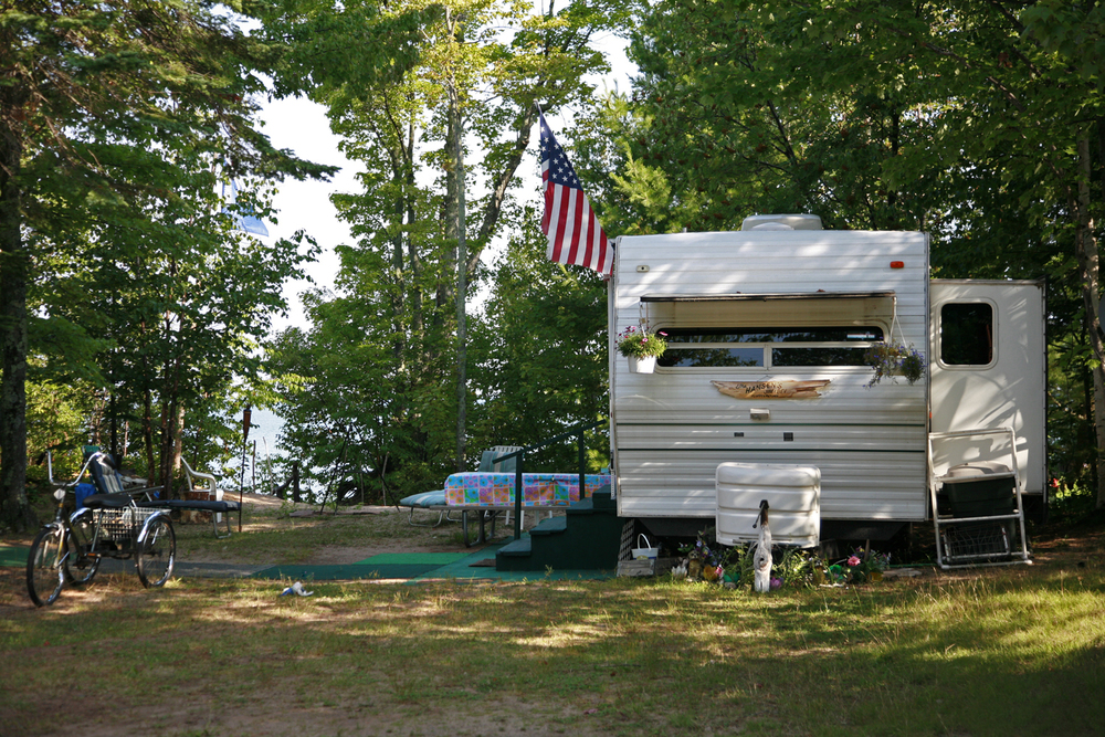 A documentary photograph of a recreational vehicle with an american flag at a camp site in the midwest of the united states