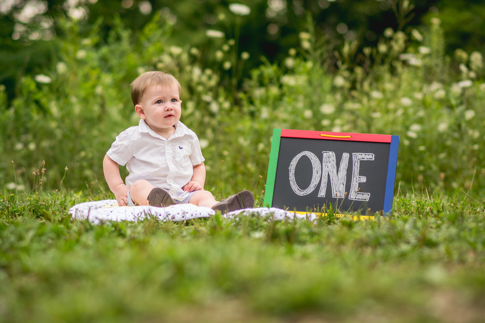 baby-one-year-old-boy-park-sign
