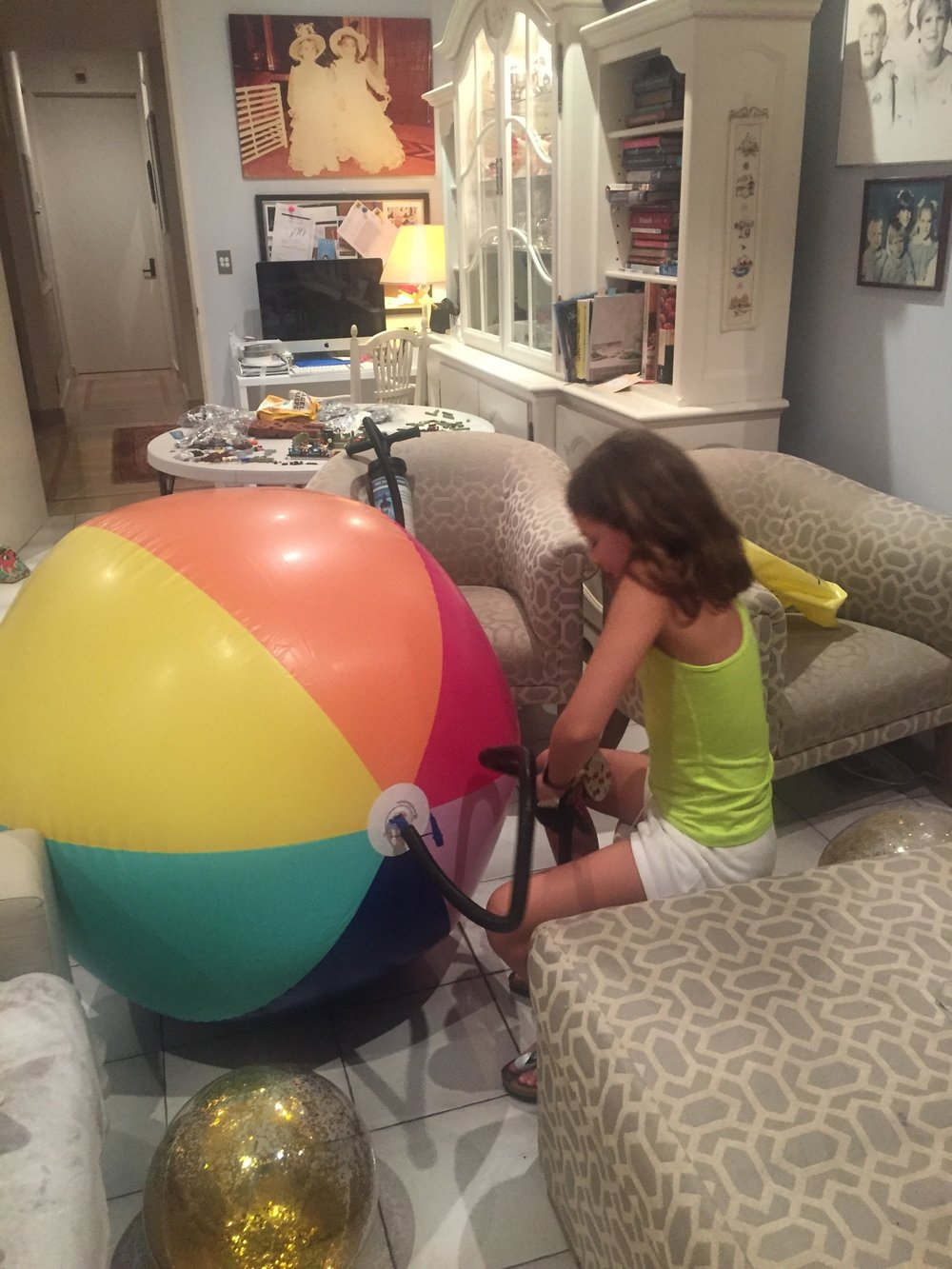 Blowing Up Rainbow Beach Balls for Neve's Rainbow Unicorn Themed Birthday Party