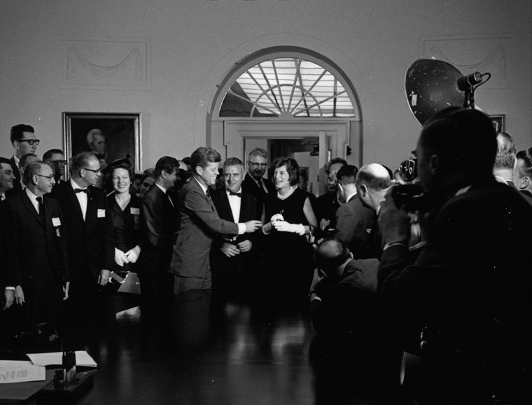 President Kennedy hands signing pen to Eunice Kennedy Shriver after signing the Maternal and Child Health and Mental Retardation Planning Amendments of 1963.