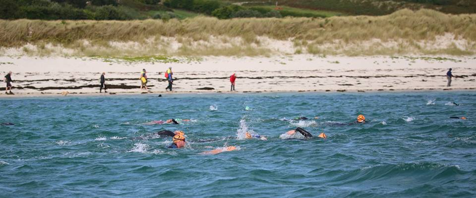 Open water swimmers battling the seas. Image courtesy of Scilly Swim Challenge.