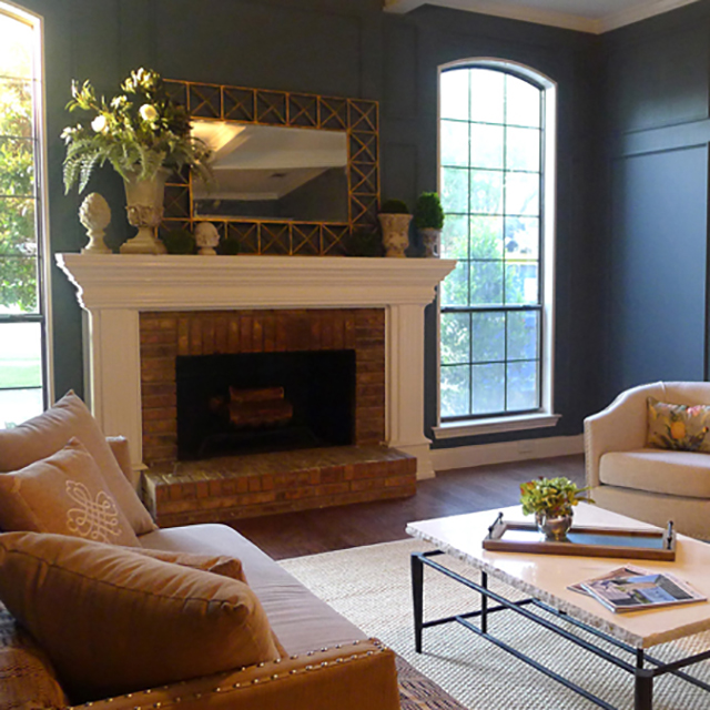 Beautiful deep blue sitting room with original brick fireplace and painted wood mantle | Pig + Tiger Renovation Plano TX