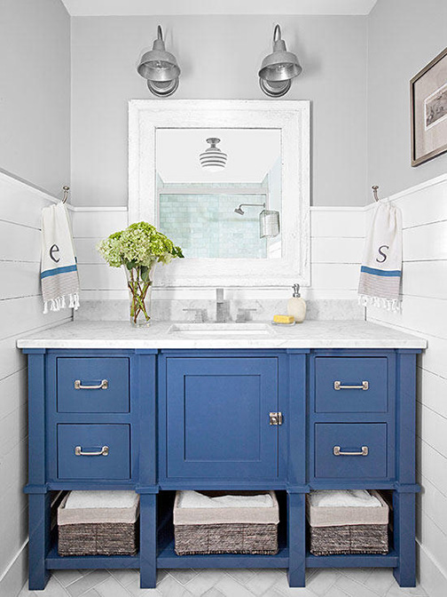 This design uses the blue cabinet, distinctive hardware, and shiplap top create a sophisticated nautical feel. the gray walls harmonize well and make me think of a misty morning on the water.