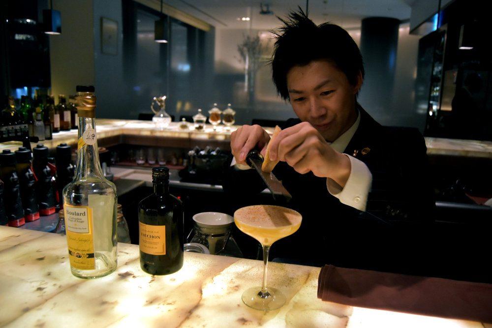 Koji-san scraping baguette topping onto a Garden of Eden cocktail
