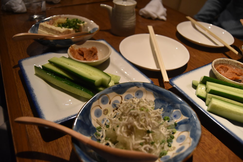 "Our ""first course"" for the moriawase was light bites including radish with small dried fish, cucumber and some (very) mildly sweet dipping sauce, and tofu. Next course was a variety of sashimi with our next sake selections."