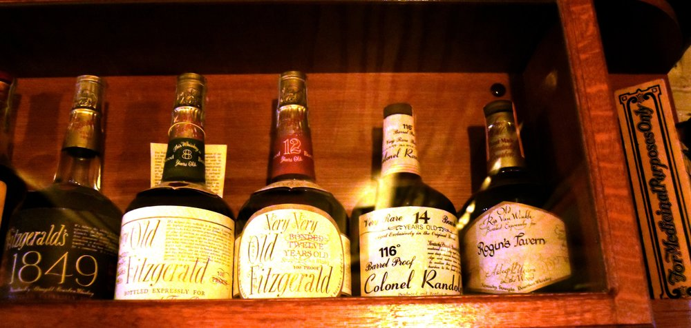 Close-up shot of some of the ancient bottles of Old Fitzgeralds and a Pappy van Winkle bottled exclusively for Rogin's Tavern.