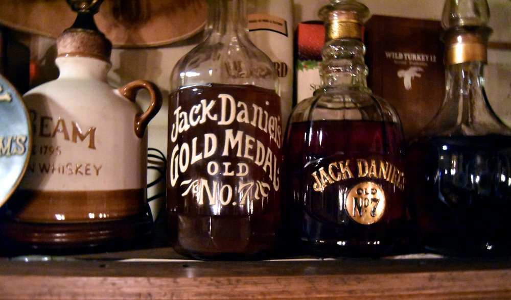 Closeup of old bottles of Jim Bean and Jack Daniels