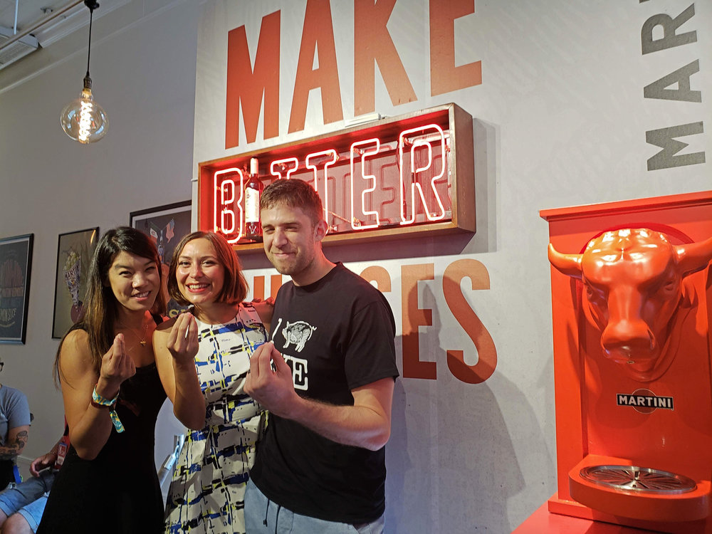 "With Roberta Mariani, in front of the Negroni-making bull sculpture and a ""Make Bitter Choices"" sign"