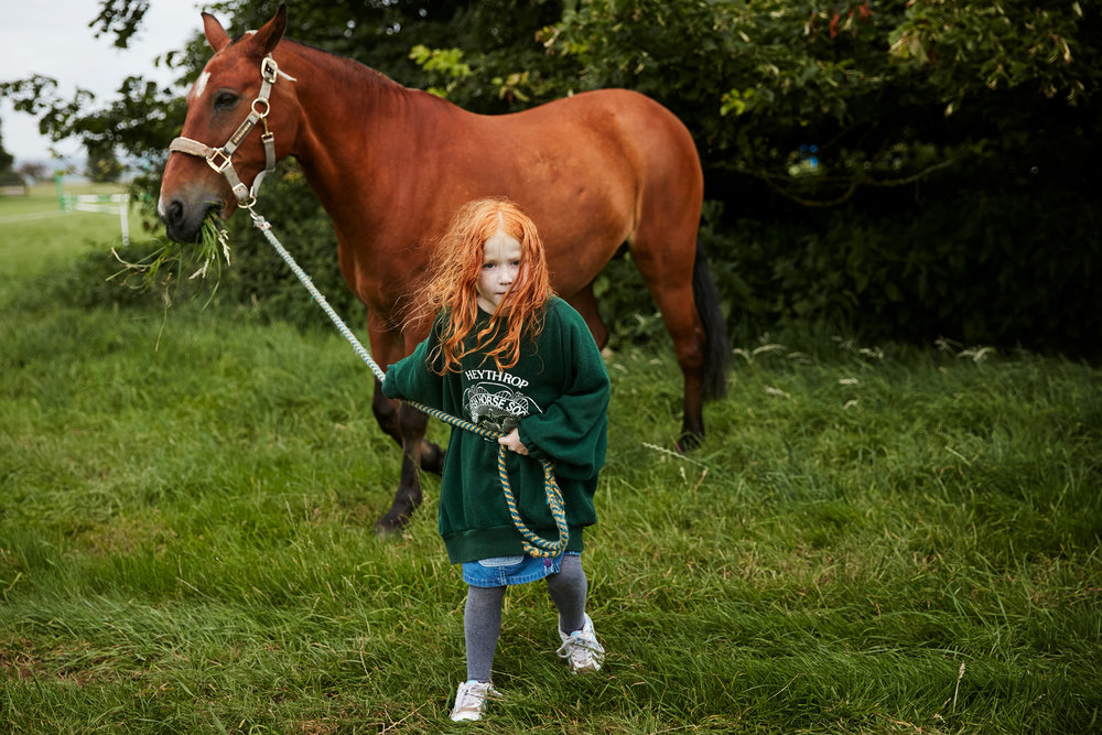 Red haired girl with pony at pony club camp photographed by Chris Floyd represented by Flock