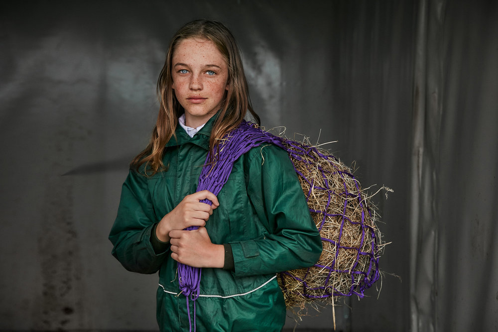 Girl with hay at pony club camp photographed by Chris Floyd represented by Flock