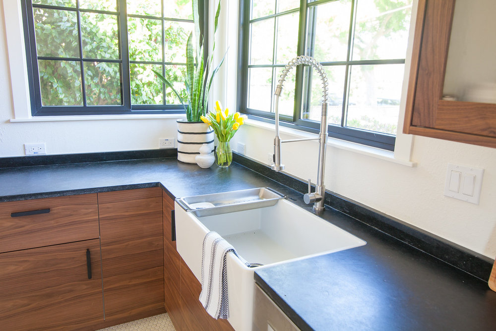After: The formerly corner-situated sink is re-positioned for easier access and replaced with a new Farmhouse Fireclay sink and flanked by new windows.