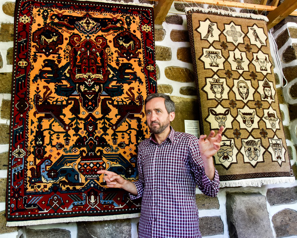 Grigor Machanents, founder of CAU.  The rug on your left is a unique design of ancient pagan origin.  On your right is a rug with important symbols of the Armenian Christian church.  Both are important parts of the long, rich history of Armenia.