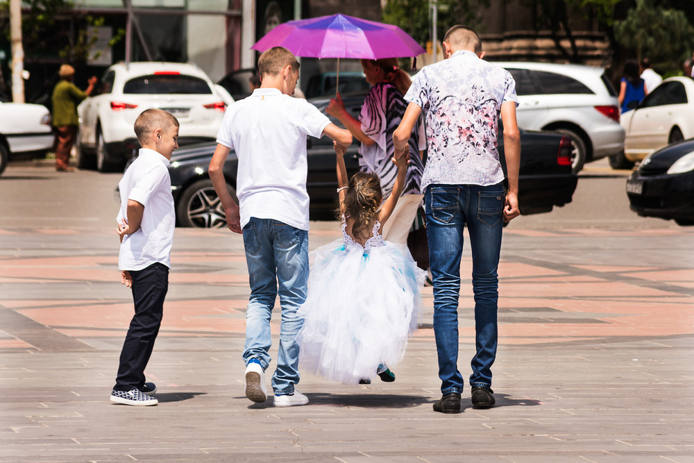 Brothers escort the flower girl to a waiting car after one of the many weddings