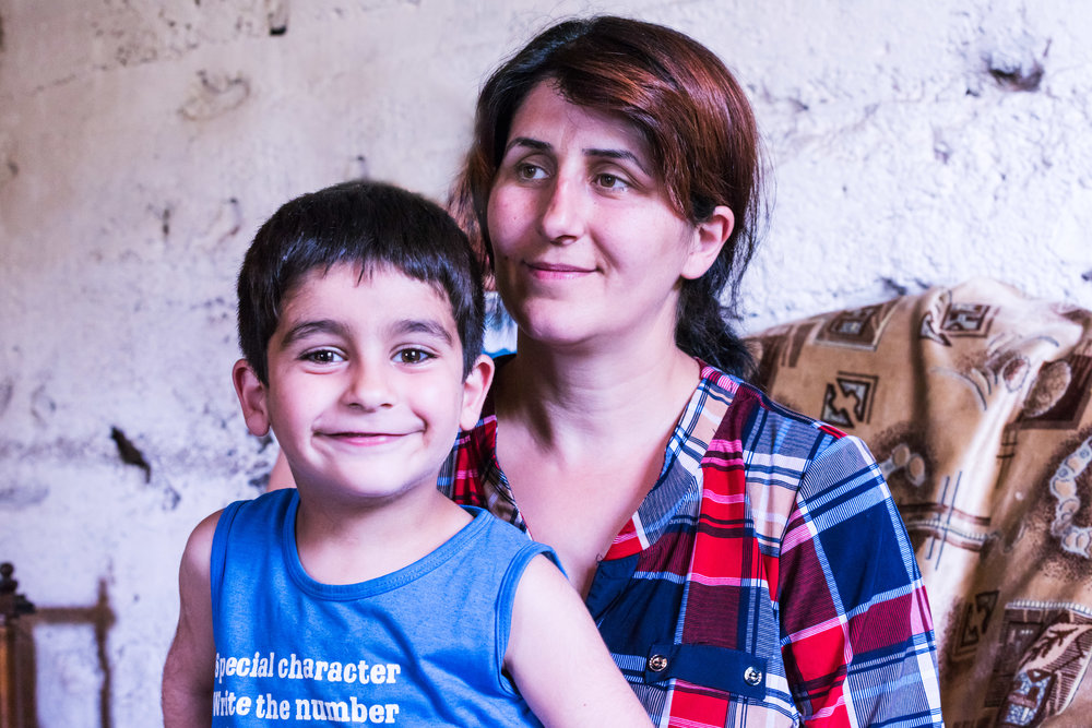 Tatev with her son, at her home where she uses the sewing machine provided by FAR to earn extra money to help her family.