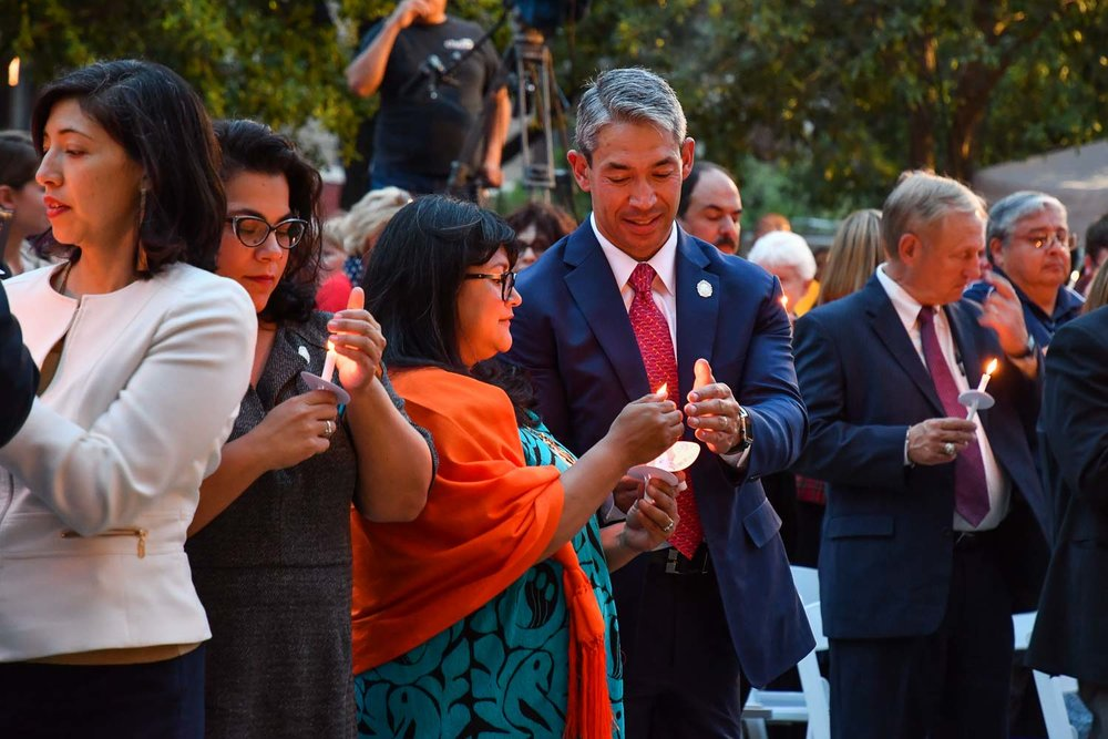 Mayor Ron Nirenberg lights a candle using the flame of his wife, Erika Prosper's candle