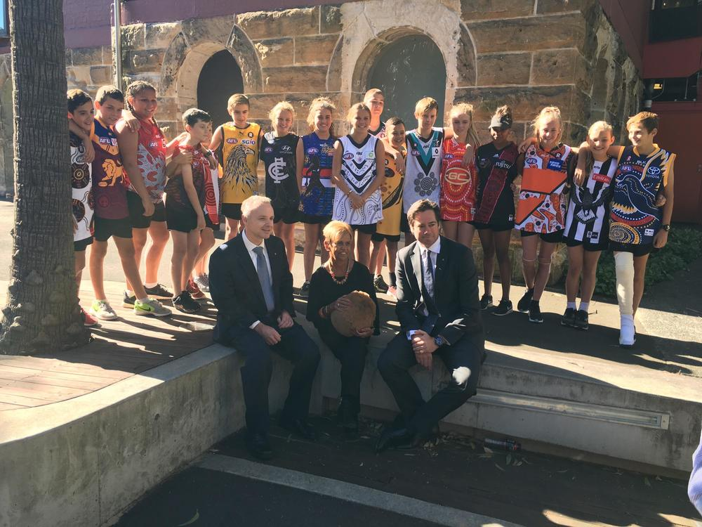 Andrew Harding, Aunty Pam and Gillon McLachlan with the children who are wearing this years Indigenous design jumpers.