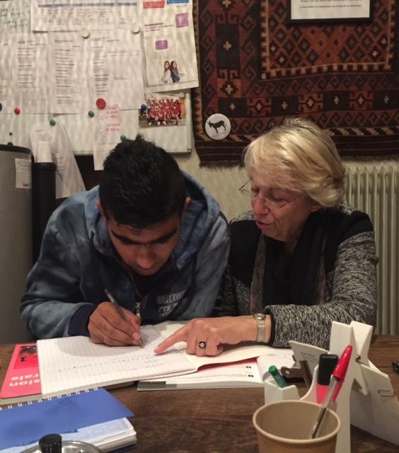 Shafiq apprend à écrire en français avec Marie-Josée. Les deux ont l'air très appliqués.