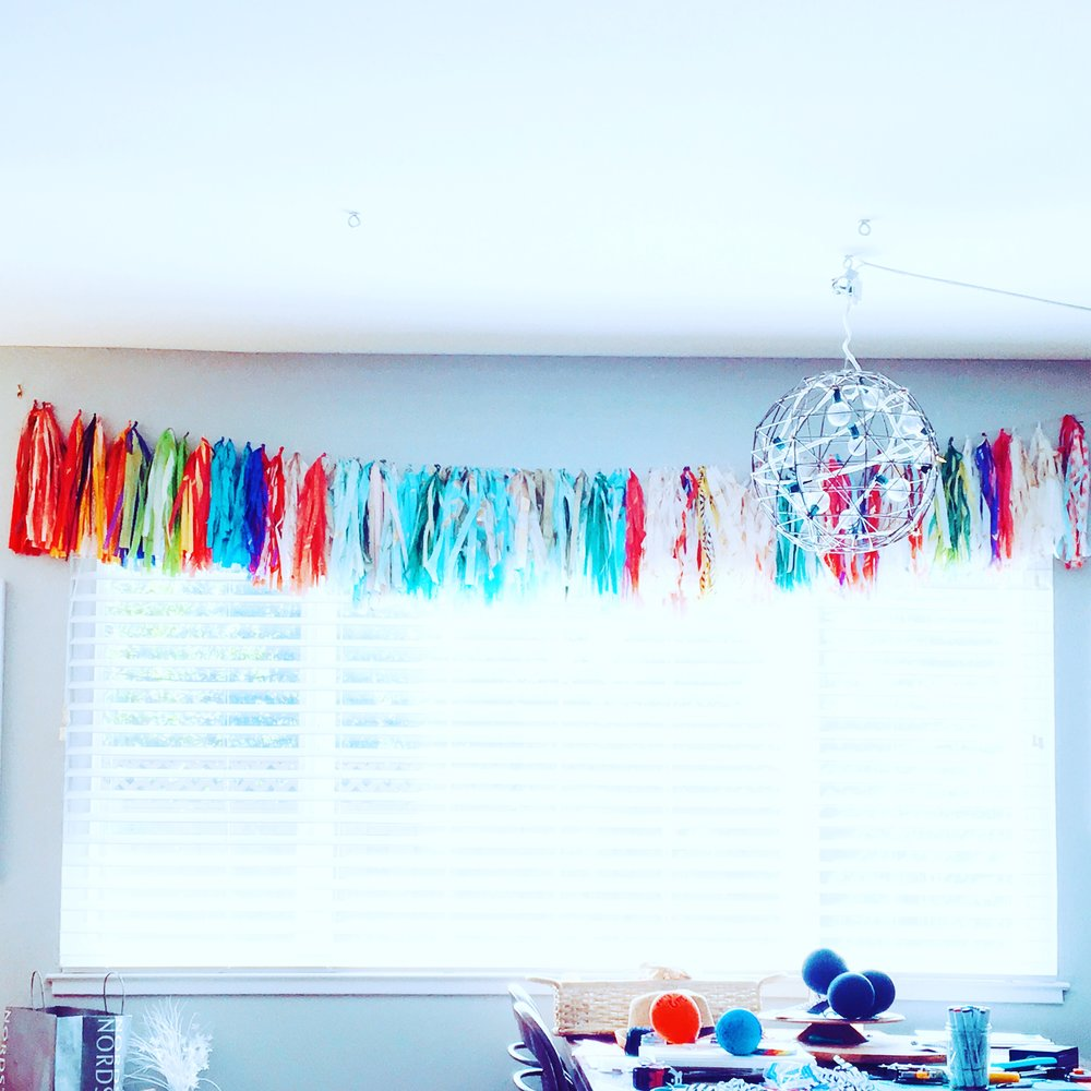 Another fun way to use festive garland is as valance over windows. - I love the sound and the airy look of them when a breeze brushes through the tassels.