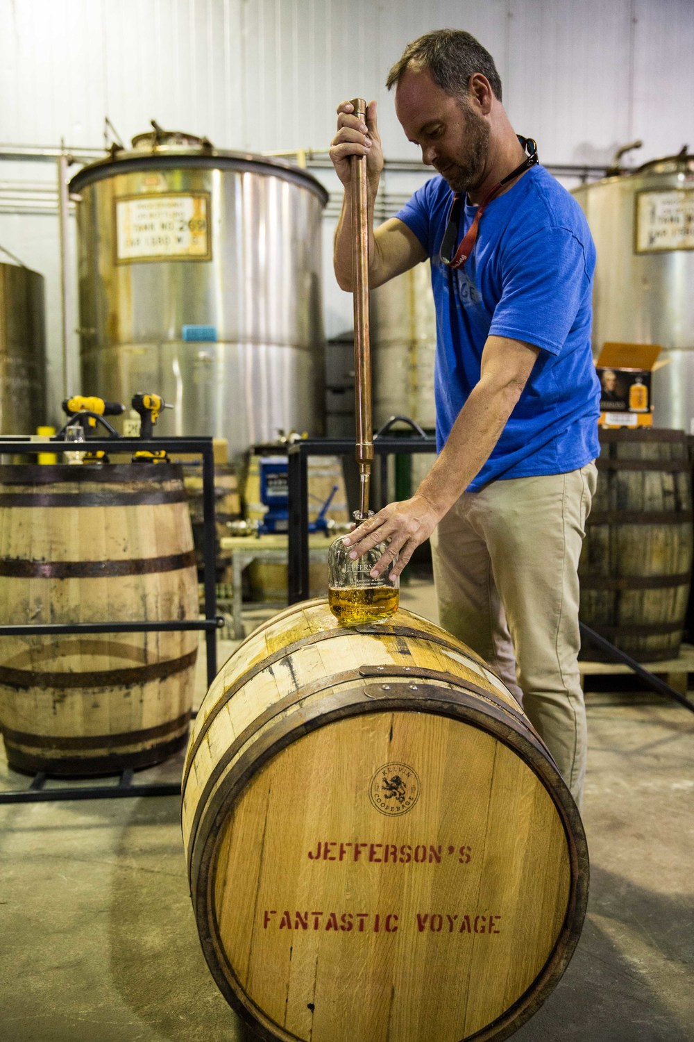 "Trey Zoeller, pulling a sample from the ""Fantastic Voyage"" barrel to test the flavor profiles before the journey."