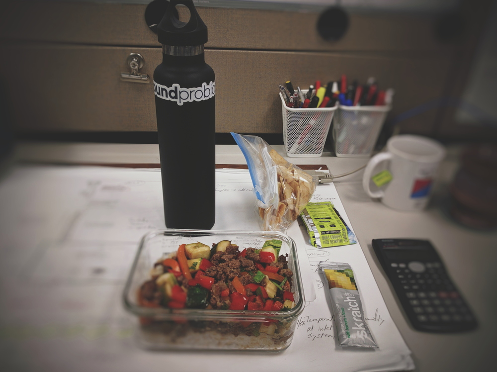 Lunch at my desk. Leftover Korean-style beef and veggie rice bowl, a Skratch labs drink to top off hydration and electrolytes, some plain pita chips for a salty afternoon snack, and a Picky Bar in case I need a little something extra. Calculator included to establish the nerdy engineer mood.