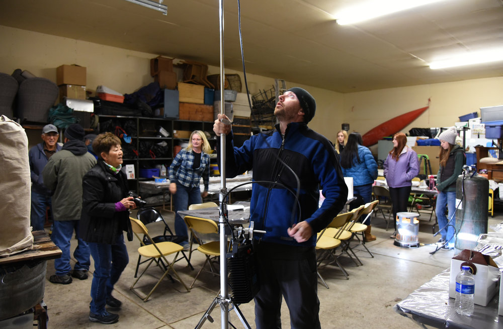 Audio/grip Slade Williamson adjusts a light while producers and ADs work to arrange the extras for the next shot.