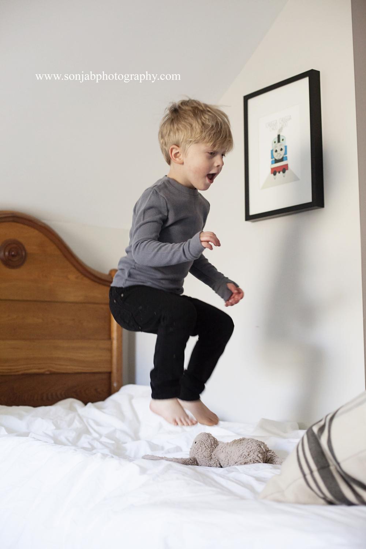 cincinnati photographer jumping on bed.jpg