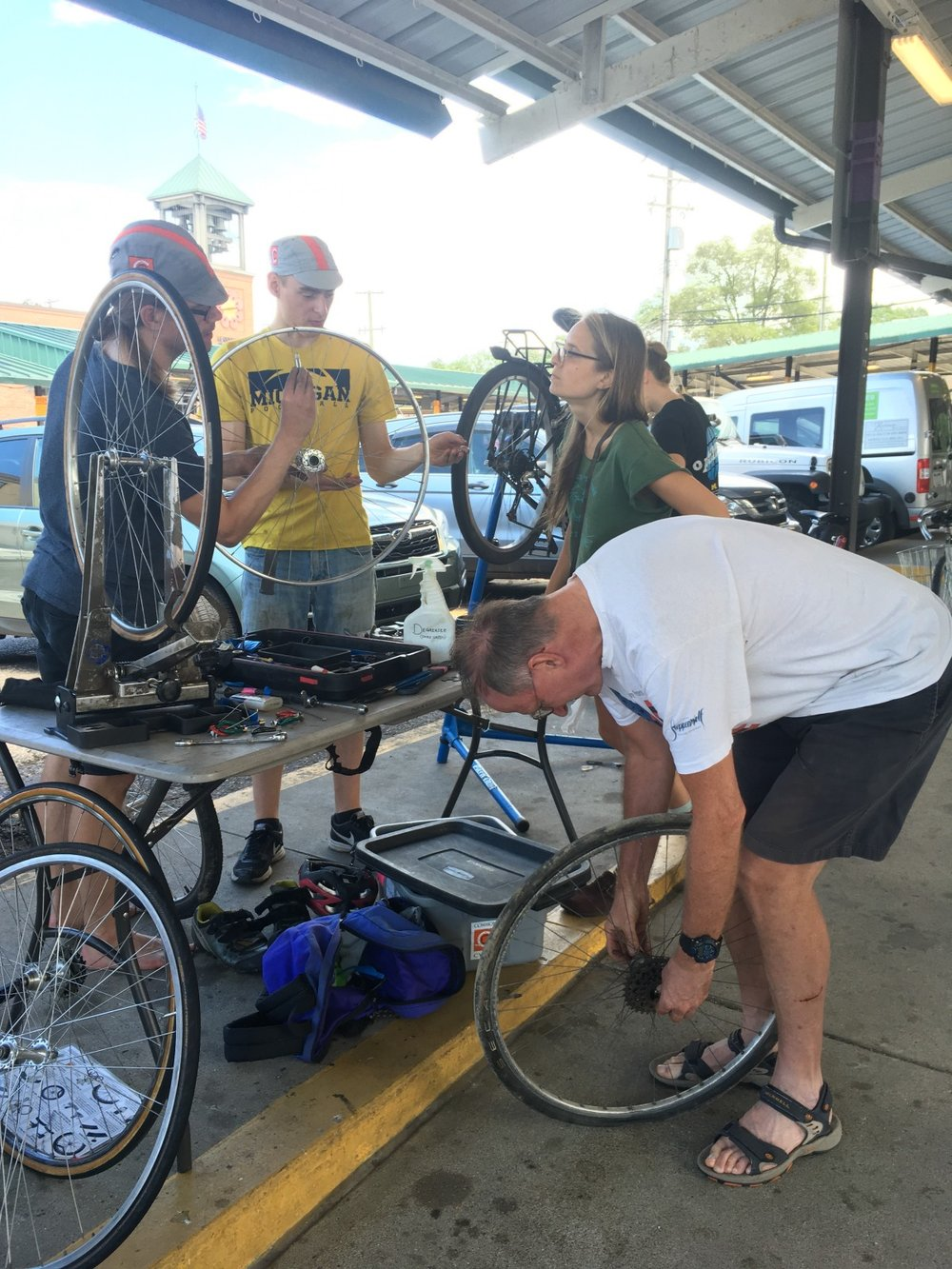 Andrew works with Common Cycle board member Ian, apprentice Simone, and a patron at Common Cycle's typical mobile repair stand in Kerrytown.