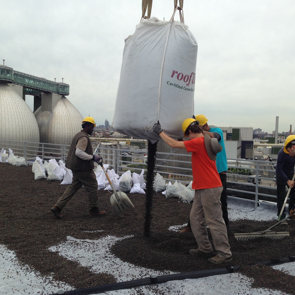 Green roof workers pouring a crane-suspended bag of drainage gravel over the initial protective layers.