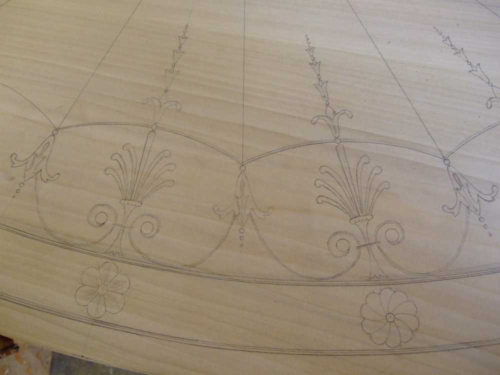 Freehand drawing of perimeter inlay details on the poplar pattern of the top.