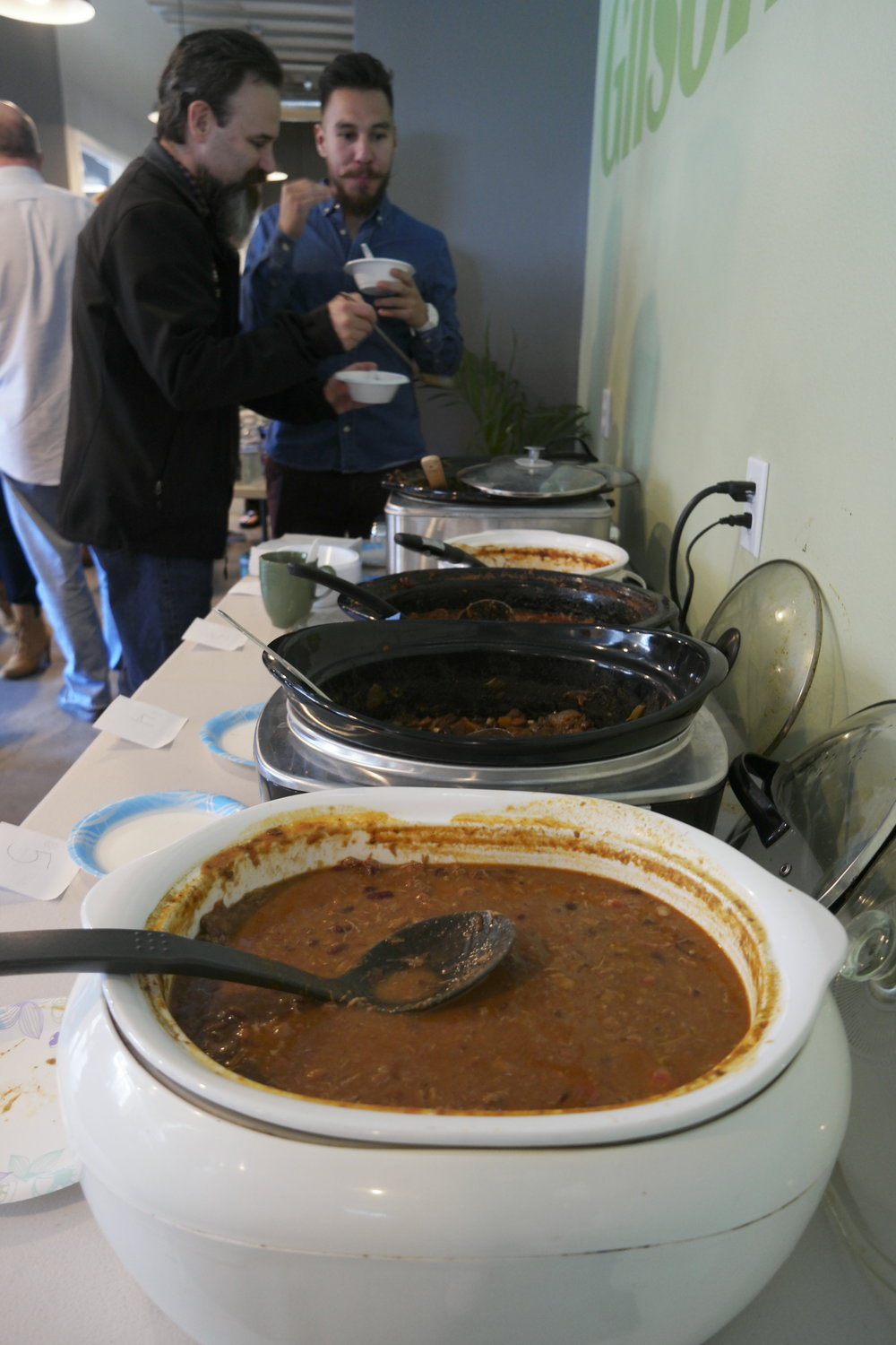 Managing Attorney Reed Heustis, Jr. and Department Head Alberto Flores sample some of the chili.