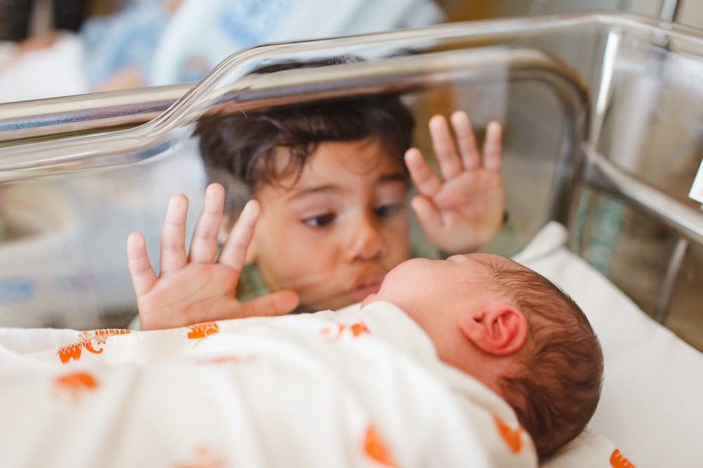 New siblings looking at each other in hospital nursery, by Twinkle Start, a Santa Maria Child Photographer
