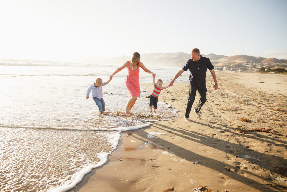 A family of four are holding hands and running through the surf on a beautiful evening , in this family photography session by Twinkle Star Photography, an Avila Beach family photographer