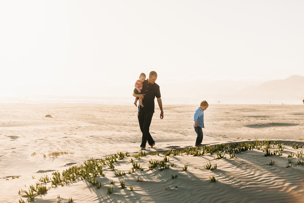 A father and his two young sons walk along the beach with the setting sun behind them in a family photography session by Twinkle Star Photography, a Santa Maria family photographer
