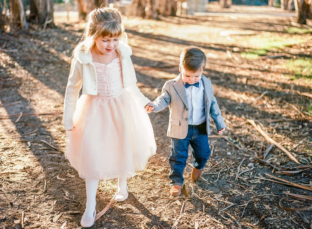 A girl in a dress and her younger brother in a jacket and tie, hold hands as they walk through a forrest path, in a child photography session by Twinkle Star, a San Luis Obispo child photographer