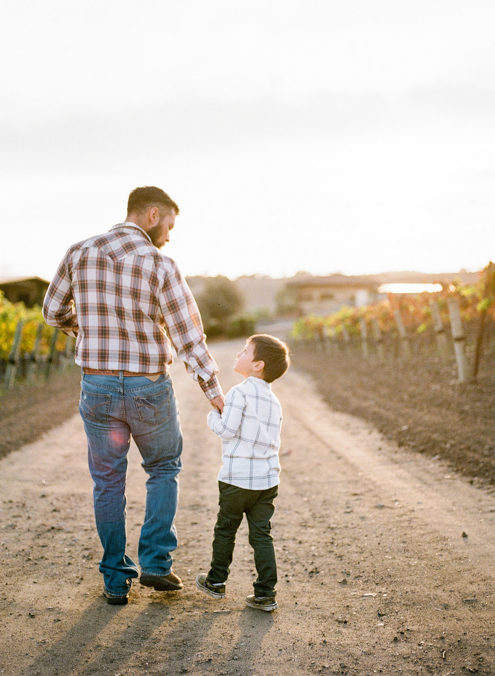 A father and son walking hand in hand down a dirt road, with the sun setting beyond them in this family photography session by Twinkle Star Photography, an Arroyo Grande child photographer.
