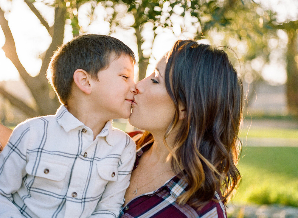 A mother and young son sharing a playful kiss, with the sun setting beyond them in this family photography session by Twinkle Star Photography, an Nipomo California child photographer.