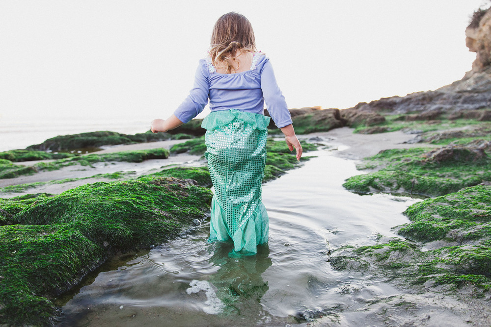 A cute young girl wearing a mermaid costume, walks away from the camera in this child session by Twinkle Star Photography, a Santa Maria California family film photographer.