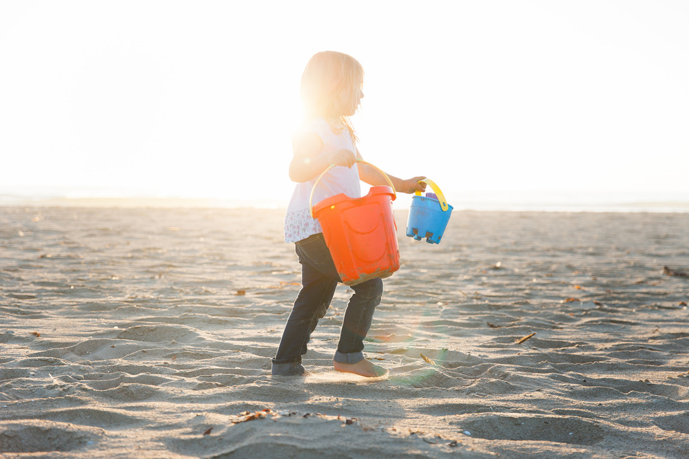 A young girl runs in the sand with buckets in each hand and beautiful sunlight over her shoulder in this child session by Twinkle Star Photography, an Orcutt California family film photographer.