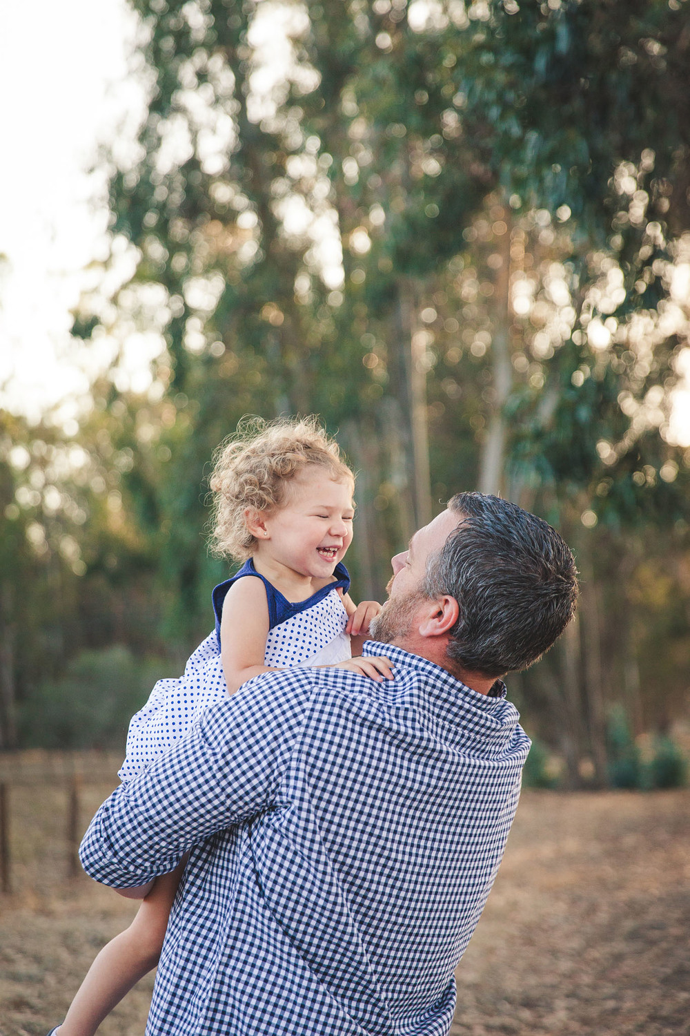A father hold his young daughter in his arms over his head while she laughs with delight in this family session by Twinkle Star Photography, a San Luis Obispo California family film photographer.