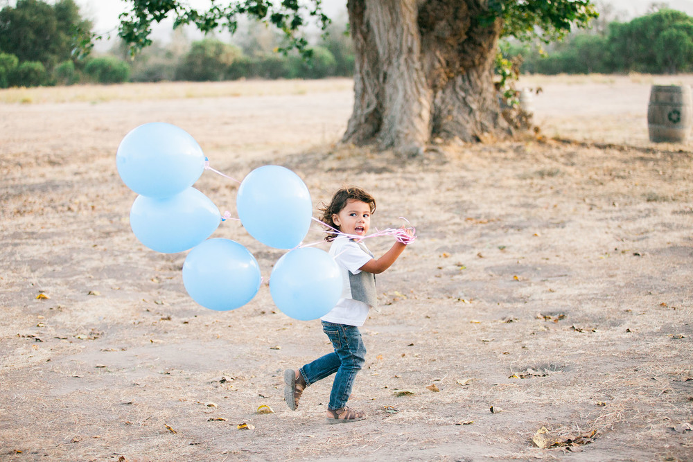A young boy runs on a forest path with five big, light blue balloons in his hand in this child session by Twinkle Star Photography, an Arroyo Grande California family film photographer.