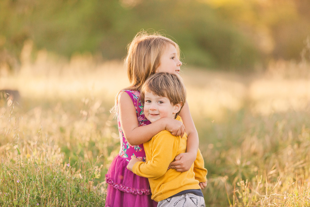 An older sister hugs her baby brother while standing in a picturesque, open field, in this child session by Twinkle Star Photography, an Avila Beach California family film photographer.