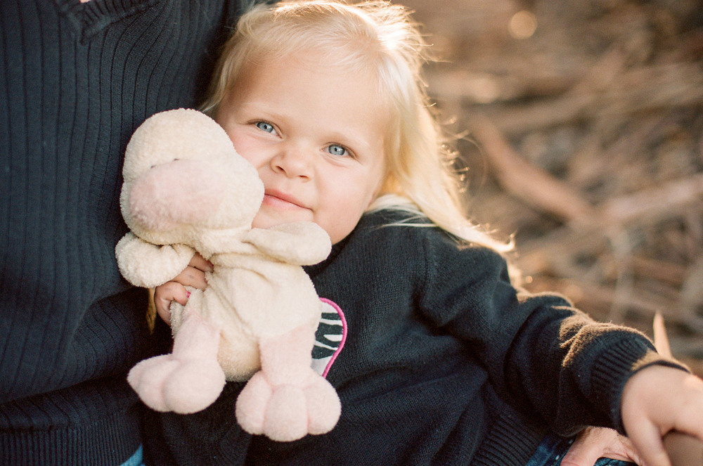 An adorable blue eyed, blonde haired little girl holds her stuffed animal in this child session by Twinkle Star Photography, an Santa Maria California child film photographer.