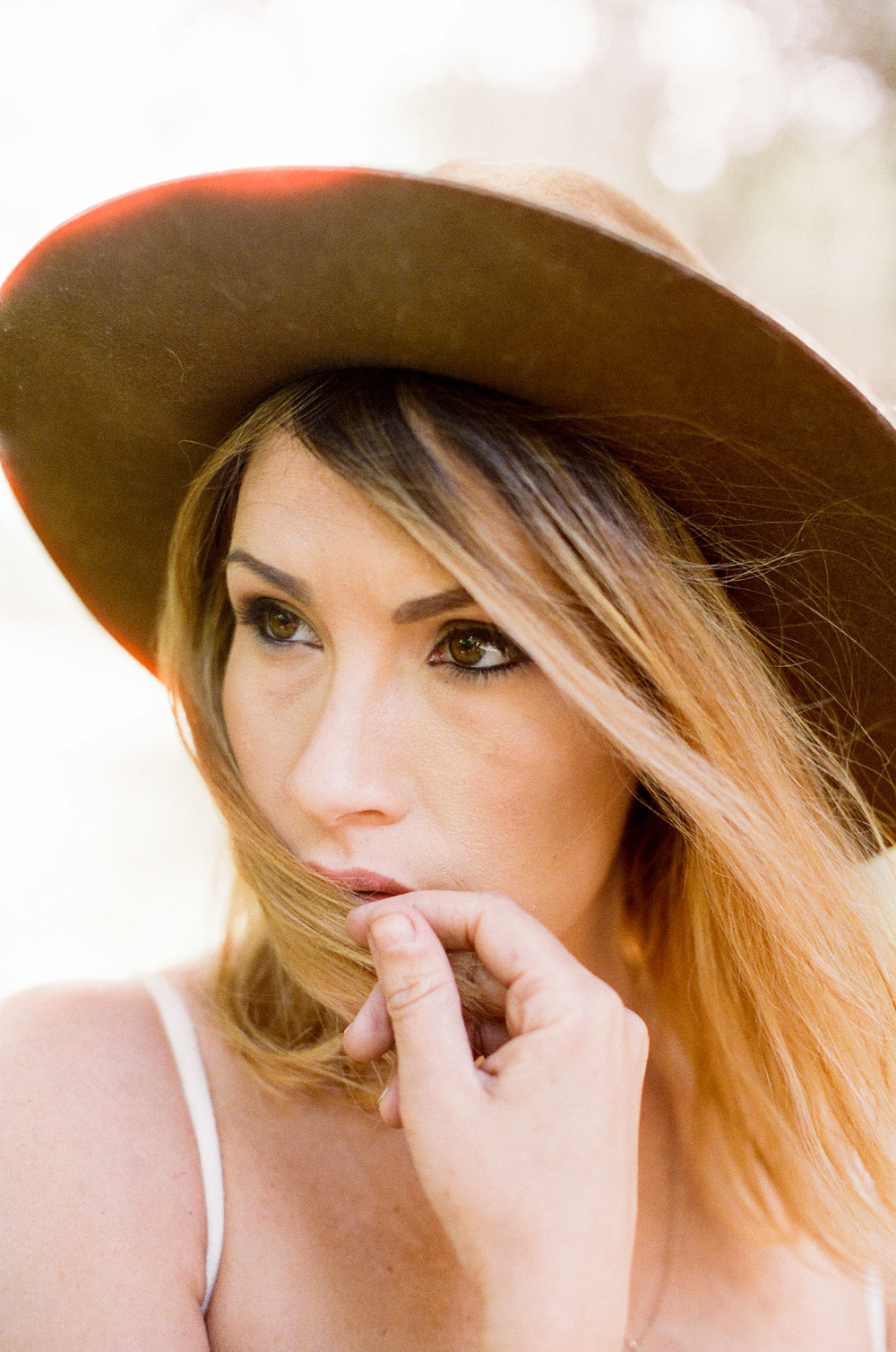A beautiful woman in a hat, has her blonde hair blowing in the wind in this family photography session by Twinkle Star Photography, an Orcutt California film photographer.