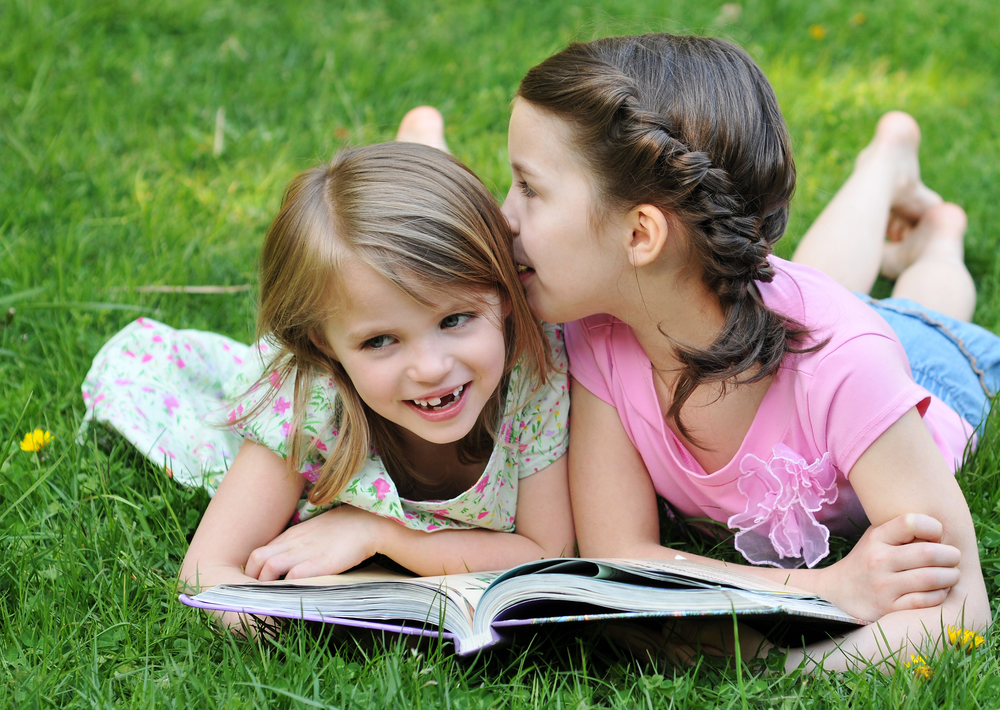 Two-young-girls-on-grass-reading-book-whispering-000005856332_Large.jpg