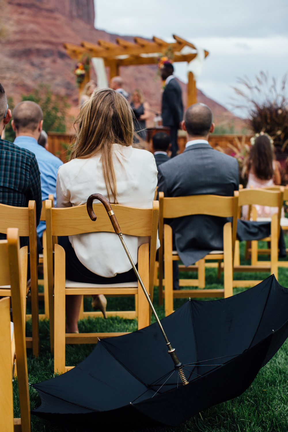 Guests candid umbrella rain rainy wedding day Red Cliffs Lodge